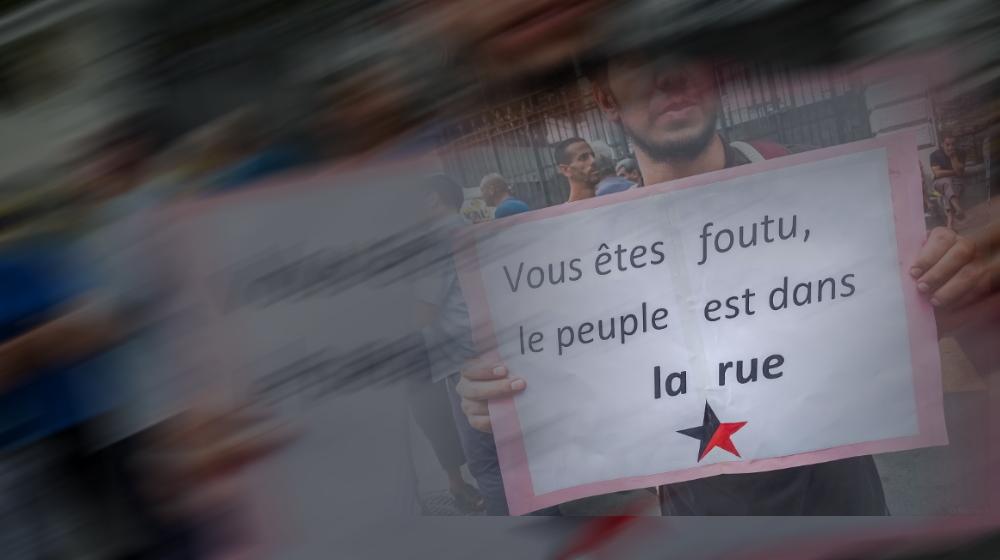 """Ein Algerier hält ein Plakat mit schwarz-rotem Stern und der Aufschrift """"Vous êtes foutu, le peuble est dans la rue"""" in die Kamera"""