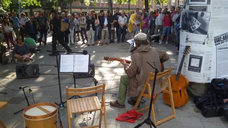 EIn Mann sitzt nebem dem Denkmal von Paulf Wulf und spielt auf einer Gitarre. Im Hintergrund stehen Zuhörer*innen