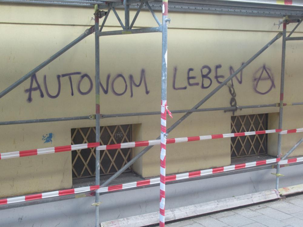 """Der Schriftzug """"Autonom Leben"""" an einer Hauswand hinter einem Baugerüst"""