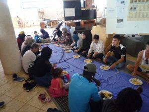 Eine Gruppe von Flüchtlingen beim Mittagessen in Habibi.Works