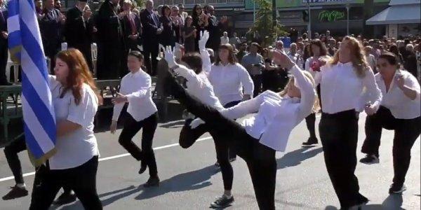 """Frauen in schwarzen Hosen und weißen Hemden demonstrieren mit einem """"silly walk"""" gegen Nationalismus und Militarismus in Griechenland"""