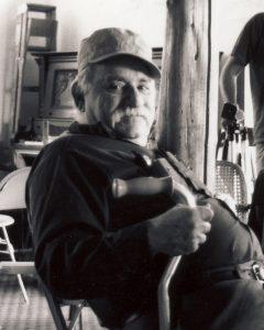 Ein wohlbeleibter Mann mit Baseballkappe und Gehstock sitzt auf einem Stuhl.