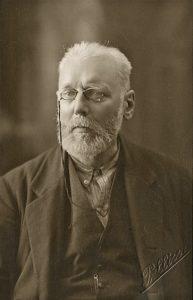Schwarzweißes Portraitphoto von Max Nettlau. Ein Mann mit Vollbart, weißem Harr und Nickelbrille