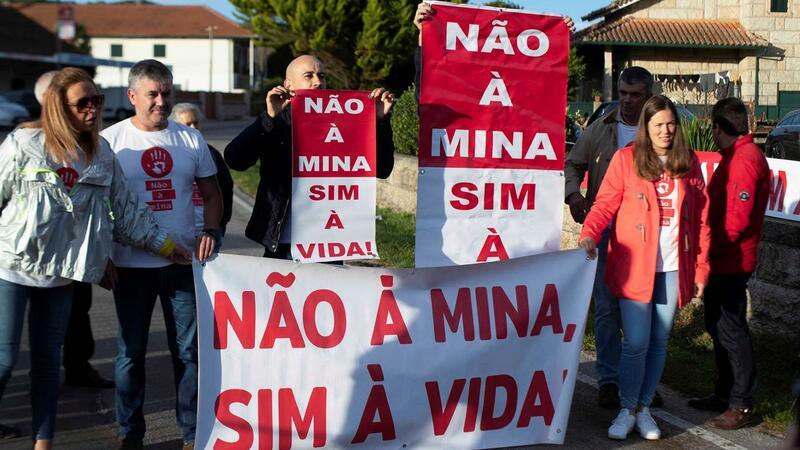 """Sieben Menschen halten Schilder und ein Transparent mit der Aufschrift: """"Nein zu den Minen, ja zum Leben!"""" auf Portugiesisch"""