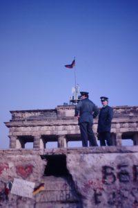 Zwei Volkspolizisten stehen im Frühjahr 1990 auf der angebrochenen Mauer am Brandenburgertor.
