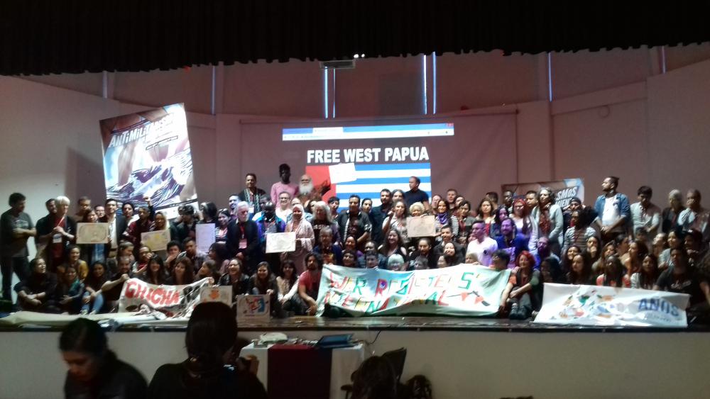 """Etwa 150 Menschen auf einer Bühne vor einem Plakat mit der Aufschrift: """"Free West Papua"""""""
