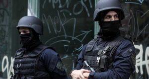 Zwei vermummte Polizisten mit Helmen, schusssicheren Westen und Waffen