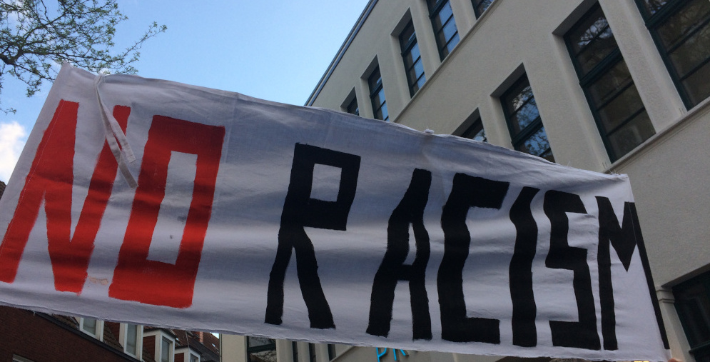 """Ein Demobanner mit dem Schriftzug """"NO RACISM"""""""