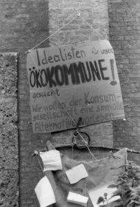Pappe mit Schriftzug: Idealisten für unser Ökokomune gesucht! Wir wollen der Konsumgesellschaft eine sinnvolee Alternative vorleben.